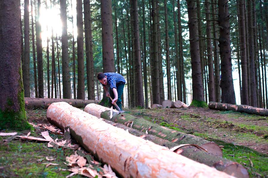 Sebastian Gutmann schält Baum für Hockerproduktion